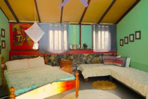 Bwa Room interior with Queen size bed and two smaller beds.